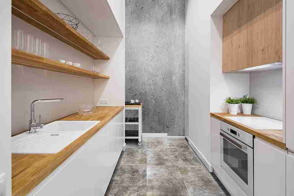 Small, functional kitchen with wooden countertop and hexagonal floor tiles
